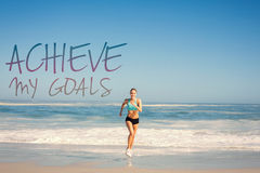 A Composite image of fit woman jogging on the beach. Fit woman jogging on the beach against achieve my goals Royalty Free Stock Images