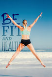 A Composite image of fit woman jumping on the beach with arms out Royalty Free Stock Photography