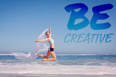 A Composite image of fit woman jumping gracefully on the beach with scarf Stock Photos