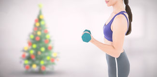 Composite image of fit woman lifting dumbbell. Fit woman lifting dumbbell  against blurry christmas tree in room Royalty Free Stock Photography