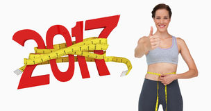 Composite image of fit woman measuring waist while gesturing thumbs up stock photo