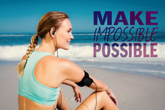 A Composite image of fit woman sitting on the beach taking a break smiling Royalty Free Stock Images