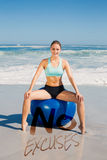 A Composite image of fit woman sitting on exercise ball at the beach Stock Photos
