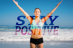 A Composite image of fit woman standing on the beach with arms up. Fit woman standing on the beach with arms up against stay positive Stock Images