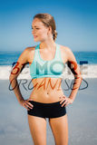 A Composite image of fit woman standing on the beach with hands on hips Royalty Free Stock Images