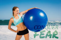 A Composite image of fit woman standing on the beach holding exercise ball Royalty Free Stock Photos