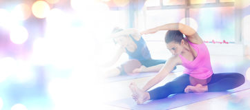 Composite image of fit women doing stretching pilate exercises. Fit women doing stretching pilate exercises against glowing background Royalty Free Stock Image