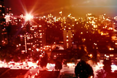 Composite image of flared figure. Flared figure against defocused image of cityscape at night Stock Photos
