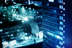 Composite image of flared figure. Flared figure against illuminated buildings in city at night Royalty Free Stock Images