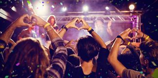Composite image of flying colours. Flying colours against crowd making heart shape with hands during performance Stock Images