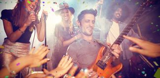 Composite image of flying colours. Flying colours against guitarist performing by crowd at nightclub Stock Photography