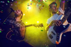 Composite image of flying colours. Flying colours against low angle view of guitarists performing on stage Royalty Free Stock Photography