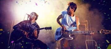 Composite image of flying colours. Flying colours against male guitarists performing on stage Stock Photos