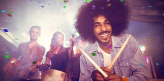 Composite image of flying colours. Flying colours against portrait of drummer holding drumsticks at nightclub Royalty Free Stock Photos