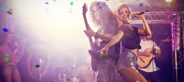 Composite image of flying colours. Flying colours against singer with guitarist performing at concert Stock Image
