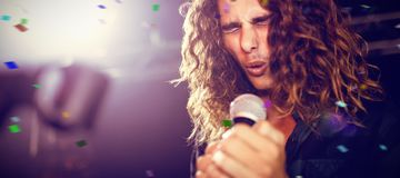 Composite image of flying colours. Flying colours against young male singer performing at nightclub Royalty Free Stock Photography