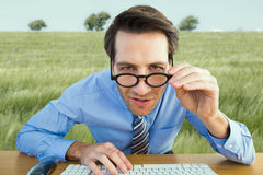 Composite image of focused businessman holding his glasses Royalty Free Stock Photography