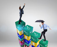 Composite image of focused businessman holding umbrella and balancing Stock Images