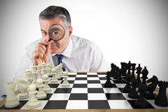 Composite image of focused businessman with magnifying glass Stock Image