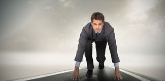 Composite image of focused businessman ready to race Royalty Free Stock Image