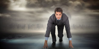 Composite image of focused businessman ready to race Stock Photo