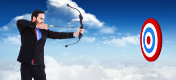 Composite image of focused businessman shooting a bow and arrow Royalty Free Stock Photo