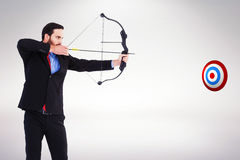 Composite image of focused businessman shooting a bow and arrow Stock Image