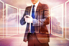 Composite image of focused businessman texting on his mobile phone Royalty Free Stock Image
