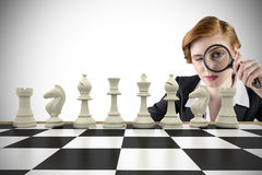 Composite image of focused businesswoman with magnifying glass Royalty Free Stock Photography