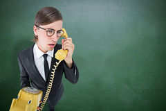 Composite image of focused geeky businessman on the phone Royalty Free Stock Photo