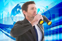 Composite image of focused handsome businessman holding binoculars Stock Photography