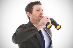 Composite image of focused handsome businessman holding binoculars Stock Image
