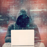 Composite image of focused male hacker using laptop Royalty Free Stock Photos