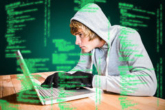 Composite image of focused man with hoodie typing on laptop Stock Images