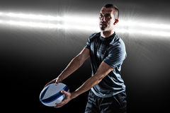 Composite image of focused rugby player looking away while holding ball Stock Images