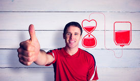 Composite image of football fan in red showing thumbs up Stock Photo