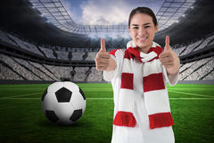 Composite image of football fan in white wearing scarf showing thumbs up Stock Image