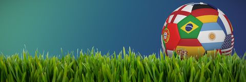 Composite image of football in multi national colours. Football in multi national colours against close-up of grass mat stock illustration