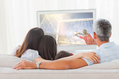 Composite image of football player kicking ball. Football player kicking ball against family watching television together on sofa Royalty Free Stock Photos