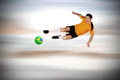 Composite image of football player in orange jumping Royalty Free Stock Photography