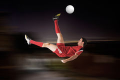 Composite image of football player in red kicking Royalty Free Stock Photos