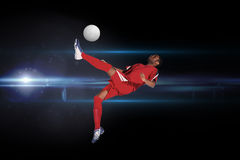 Composite image of football player in red kicking Stock Images