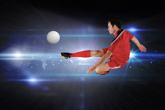 Composite image of football player in red kicking. Football player in red kicking against black background with spark Royalty Free Stock Image