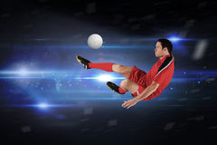 Composite image of football player in red kicking Royalty Free Stock Images