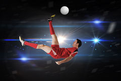 Composite image of football player in red kicking Stock Photo