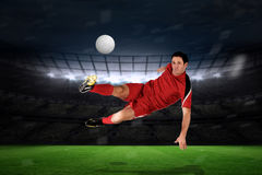 Composite image of football player in red kicking. Football player in red kicking against large football stadium with fans in yellow Stock Photo