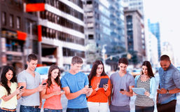 Composite image of four friends standing to the side slightly sending texts royalty free stock image