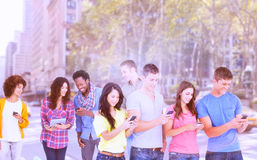 Composite image of four friends standing to the side slightly sending texts stock photography