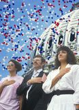 Composite image of four people at a citizenship ceremony superimposed over the U.S. Capitol and balloons Stock Photos