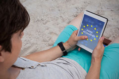 Composite image of free roaming text on european union flag. Free roaming text on European Union flag against man using digital tablet on the beach Stock Photo